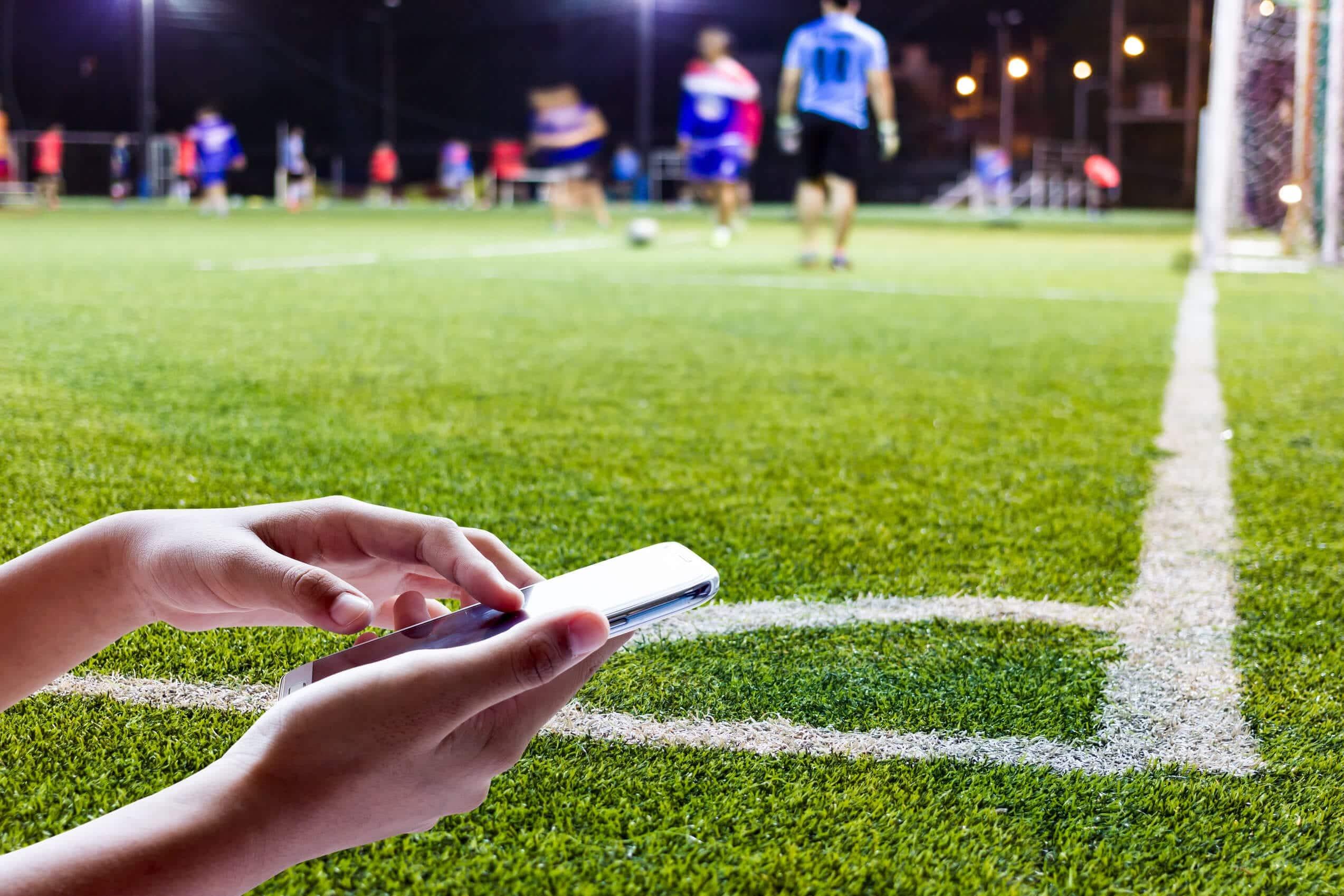 typowanie live, boisko mecz piłki nożnej, telefon