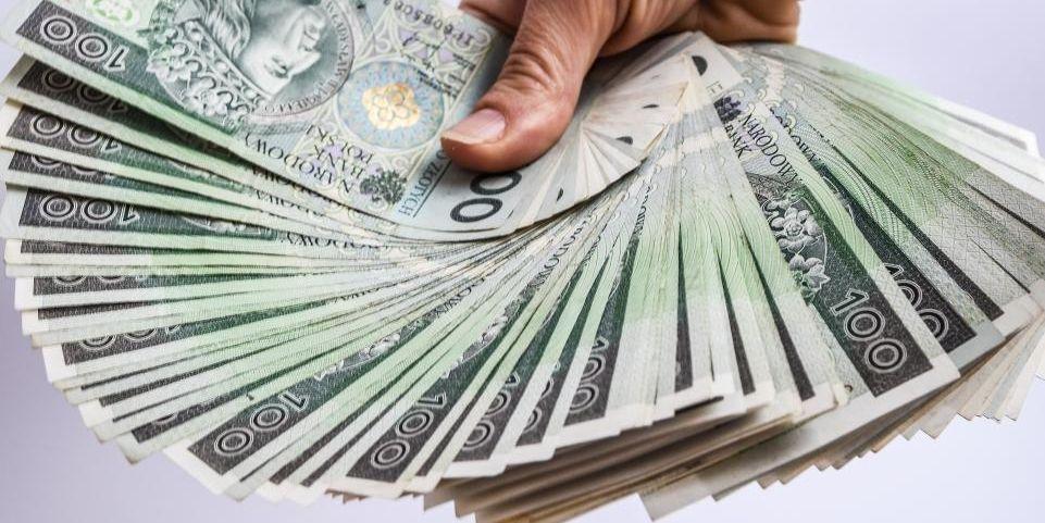 złotówki, 100 zł, ręka, pieniądze, stos pieniędzy