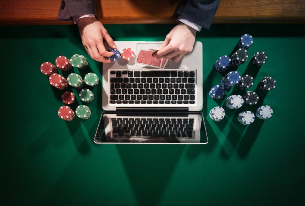 hazard online, laptop, ręka, żetony, karty, zielony stół, stół do gry